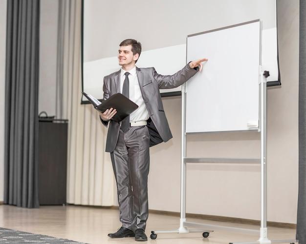 スピーカーは、現代の会議室の空白の広告委員会の前に立って、新しい金融プロジェクトのプレゼンテーションを開催します