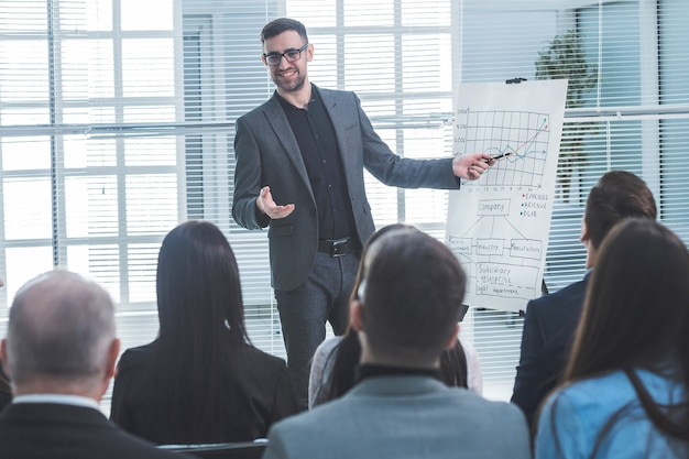 발표자는 비즈니스 프레젠테이션 중에 플립 차트를 가리키고 있습니다. 비즈니스 및 교육
