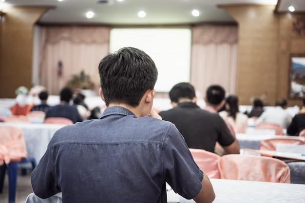 Выступающий на сцене, аудитория заднего вида слушает выступления лектора в конференц-зале или на семинаре