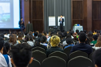 Speaker on the stage with Rear view of Audience in the conference hall or seminar meeting