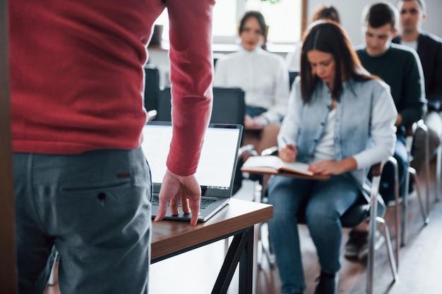 スピーカーはラップトップを使用しています。昼間の近代的な教室でのビジネス会議での人々のグループ