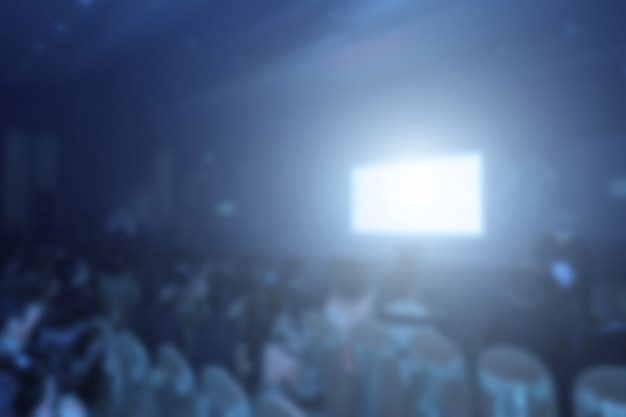Speakers on the stage with rear view of audience in the conference hall or seminar meeting