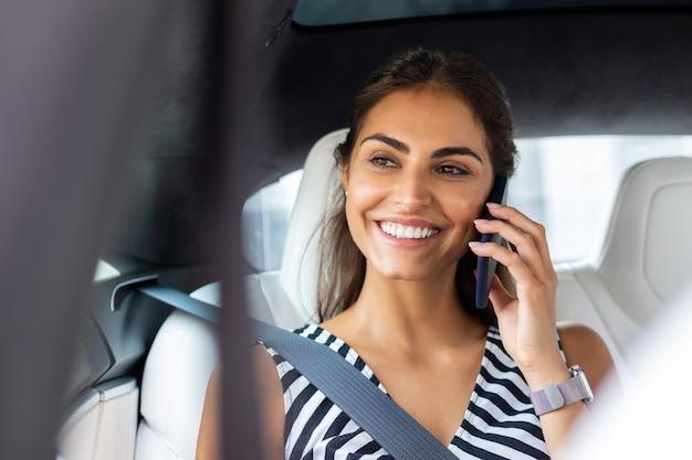 Говоря по телефону. сияющая женщина улыбается во время разговора по телефону с мужем