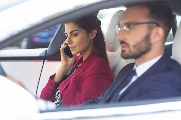 Говоря по телефону. красивая милая жена разговаривает по телефону, сидя рядом с мужем за рулем автомобиля