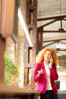 Speaking with clients. curly businesswoman speaking with clients standing near window