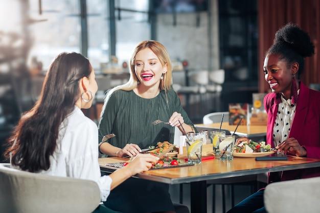 Разговор с друзьями красивая светловолосая женщина с красивым макияжем разговаривает со своими друзьями