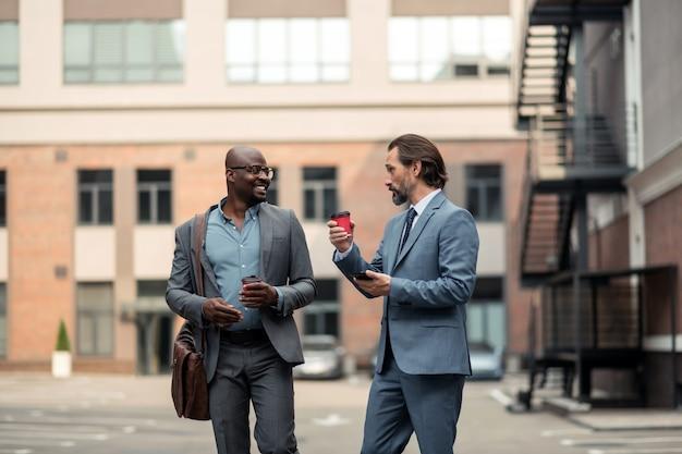 彼の従業員と話す。彼の従業員と話し、朝にコーヒーを飲むひげを生やしたビジネスマン