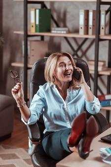 파트너와 대화. 비즈니스 파트너와 감정적 인 대화를 나누는 세련된 매력적인 성숙한 여인