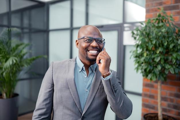 妻と話す。妻と電話で話している間微笑んでいる浅黒い肌の実業家