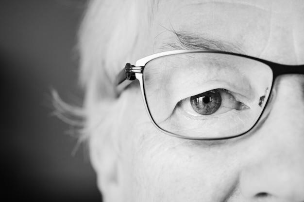 Specatacを着ている目に白い高齢者の女性のクローズアップの肖像画