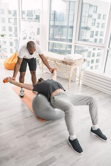 특별 활동. 의대 공에 누워 특별한 신체 운동을하는 멋진 성인 남자