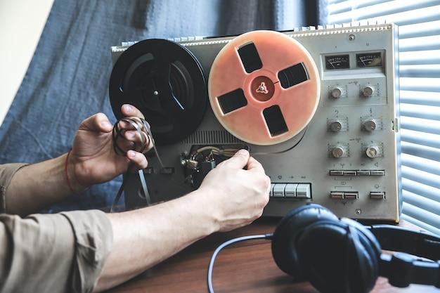特別捜査官がリールテープレコーダーのフィルムを交換します。会話をスパイしているkgb。