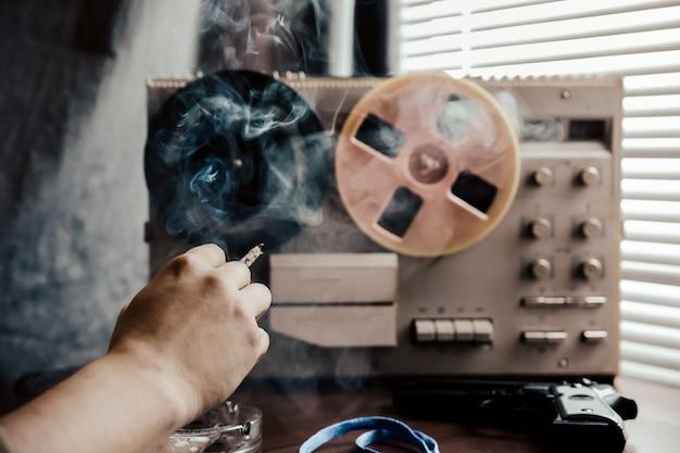 特別捜査官がオープンリールテープレコーダーでリッスンします。役員はタバコを吸っています。会話をスパイしているkgb。灰皿の近くでタバコを手に取ります。テーブルの上の銃。