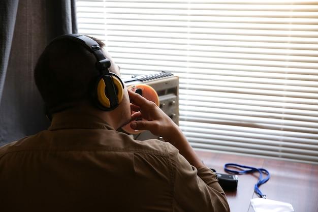 特別捜査官がオープンリールテープレコーダーでリッスンします。