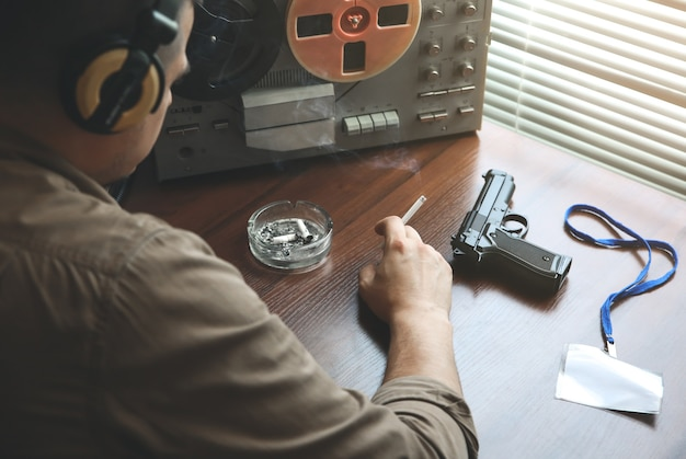 Special agent listens on the reel tape recorder. officer is smoking a cigarette. kgb spying on conversations. hand with cigarette near the ashtray. gun on the table.