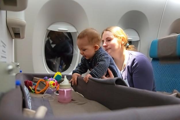 비행 중 특별한 아기 요람 유아 소녀 어머니의 첫 비행은 비행기에서 아기를 팔에 안고 있습니다.