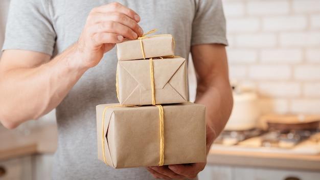 Особый день. обрезанный снимок человека, получившего подарки, открывающего бумажные пакеты ручной работы.