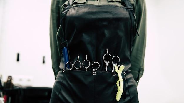 Специальное оборудование для прически. низкий угол обзора женщины-парикмахера, позирующей в парикмахерском фартуке с инструментами для укладки волос в карманах.