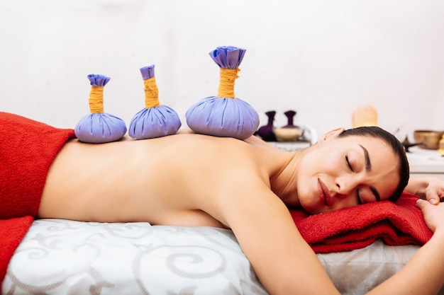 Special equipment. pleasant dark-haired woman with flawless skin resting on massage bed and having range of herbal bags on back