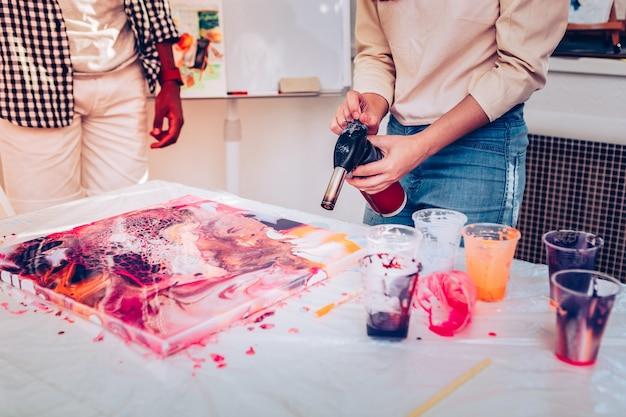 특수 장비. 특수 장비를 사용하여 놀라운 페인팅 기법을 보여주는 빨간 머리 예술가