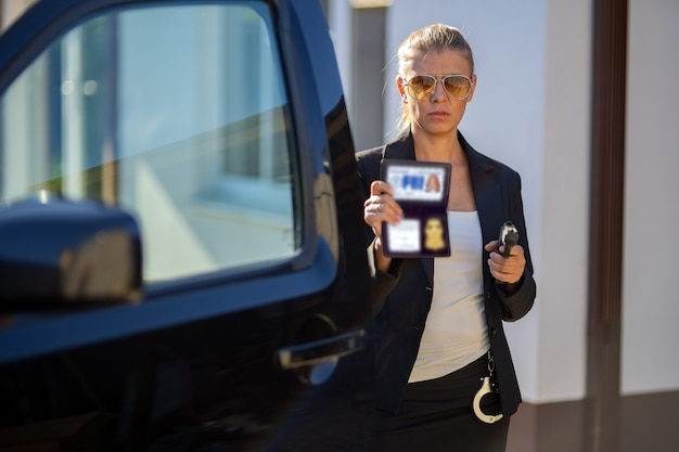Специальный агент федеральной разведки женщина в черном костюме и большой полицейской машине