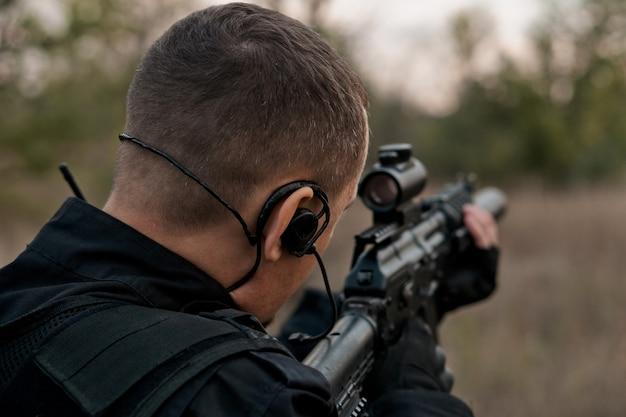 돌격 소총을 목표로 검은 제복을 입은 특수 부대 병사