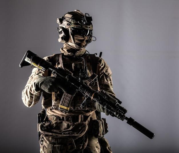 전투복을 입은 특수부대 전투기, 라디오 헤드셋, 안면 마스크, 탄도 안경을 쓴 헬멧, 흰색으로 격리된 레이저 조준기 및 소음기 서비스 라이플 스튜디오 초상화