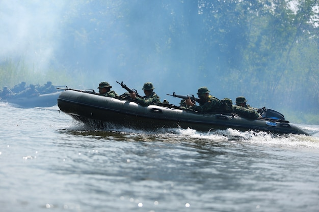 Special forces men in camouflage uniforms paddling army kayak.