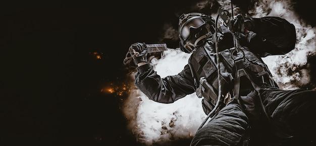 Спецназовец висит на веревке и раскачивается специальным приспособлением для разбивания окон. swat, полиция, концепция борьбы с терроризмом. дым и огонь. смешанная техника