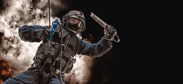 Спецназовец висит на веревке и раскачивается со специальным приспособлением для разбивания окон.