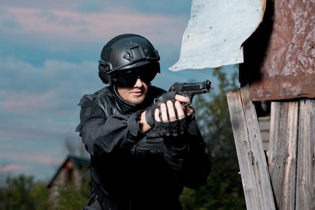 Солдат спецназа в черном униформе, шлеме и очках, целится из пистолета