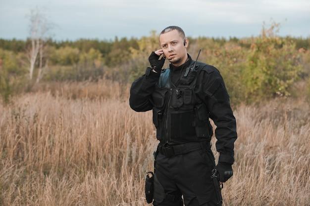 Солдат спецназа в черной форме с пистолетом говорит по радио