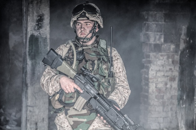 Special forces soldier, marine corps infantryman, commando fighter in helmet and body armor, equipped tactical radio, armed with service rifle with optical sight and grenade launcher in smoky ruins