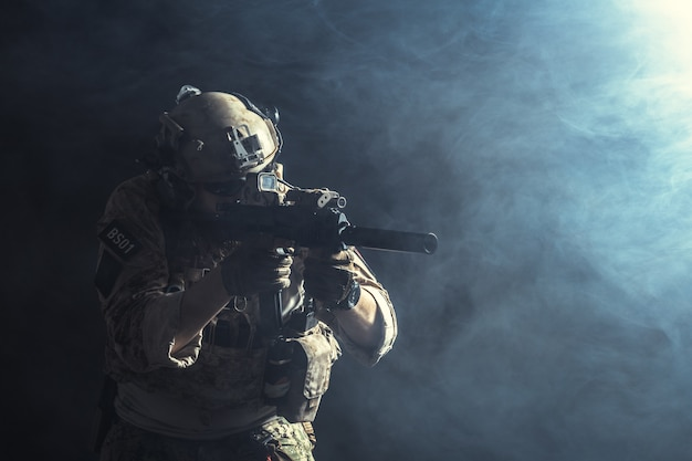 Special forces soldier with rifle on dark