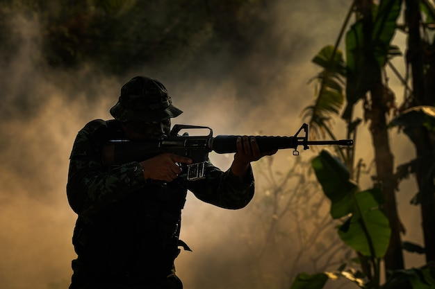 Special forces soldier with rifle, low-key lighting.