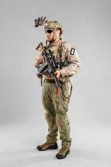 Special forces soldier with rifle on white background.
