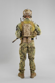 Special forces soldier with rifle on white.