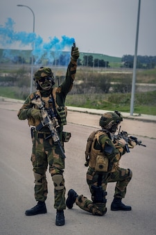 Special forces soldiers carrying out an operation using assault rifles and a blue smoke bomb