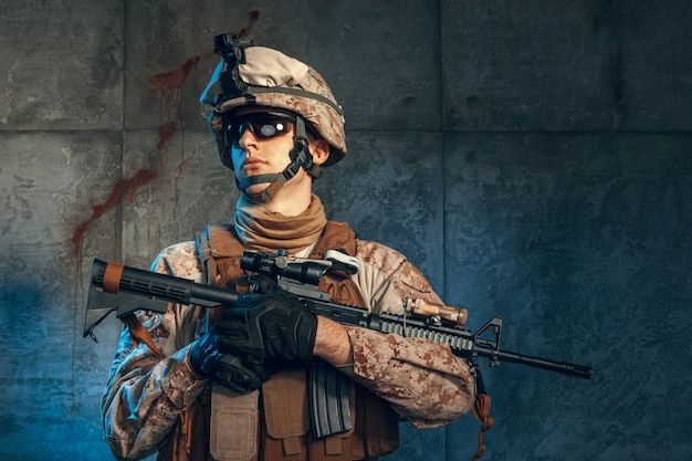 Special forces united states soldier or private military contractor holding rifle. image on a dark background