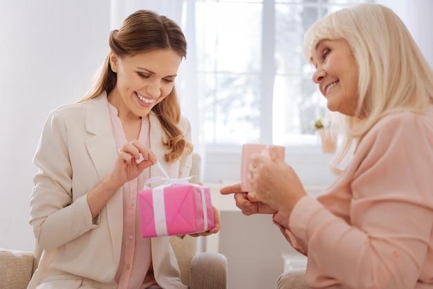 특별한 선물. 매력적인 쾌활한 긍정적 인 여자 선물 상자를 들고 안에 무엇이 궁금하면서 여는