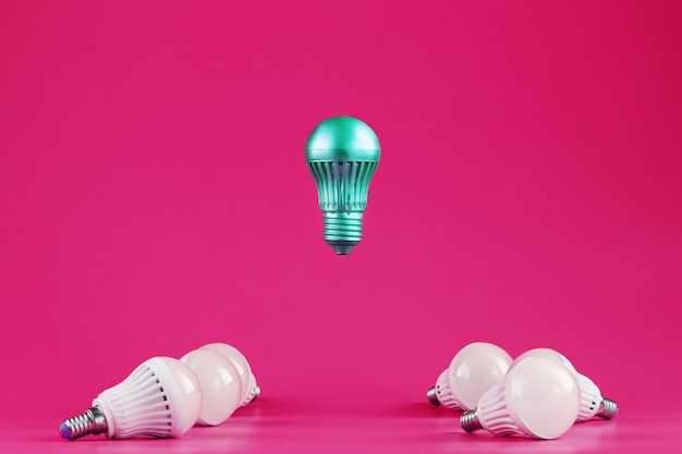 A special light bulb hovers over simple, standard white light bulbs on pink.