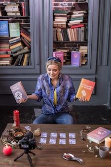 特別な文学。彼女の手で本について話している間、カメラの前に座っている素敵な感情的な女性