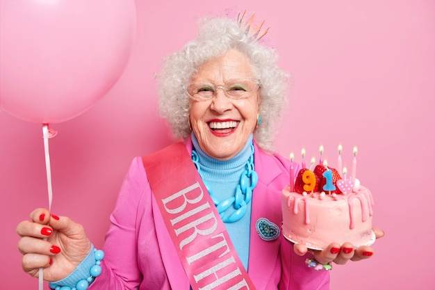 Special occasion age and festivity concept. happy smiling wrinkled senior woman holds festive strawberry cake inflated balloon prepares for party or birthday celebration expresses good emotions