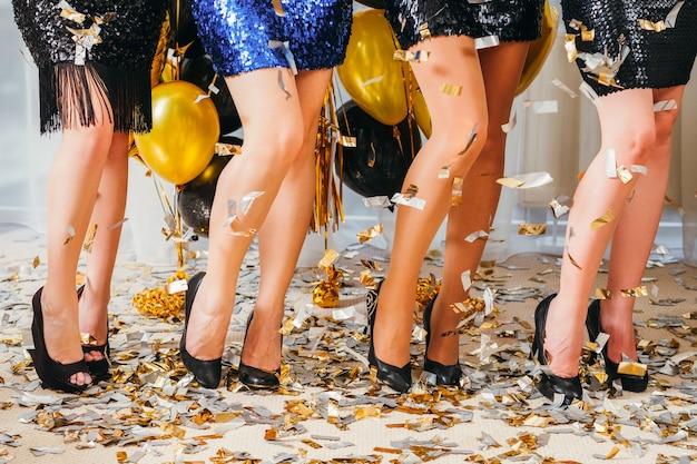 Особый случай. обрезанный снимок девушек, позирующих в мини-юбках на каблуках. красивые женские ножки. конфетти вокруг.