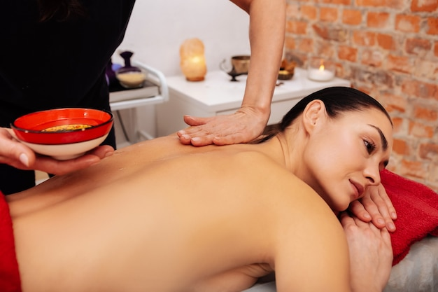 Special oil. masseuse in black uniform carrying bright bowl with oil in one hand and touching client back with another