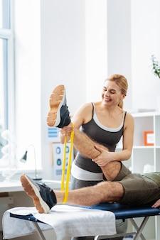 特別な身体活動。彼女の患者の足を持ち上げながら笑ってうれしそうなポジティブな女性