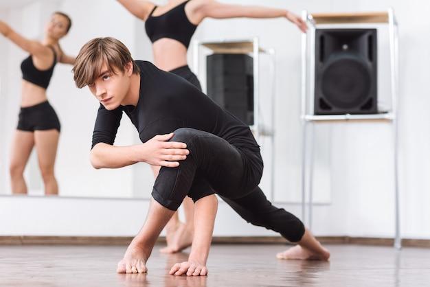 특별한 위치. 댄스 홀에서 운동하는 동안 바닥에 앉아 운동에 집중하는 잘 생긴 대단한 남성 댄서