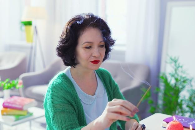 特別な匂い。テーブルに座っている間アロマスティックを保持している素敵な黒髪の女性