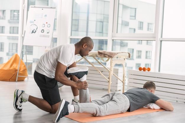 특별한 운동. 그의 다리를 들어 올리는 동안 요가 남자에 누워 즐거운 잘 생긴 남자