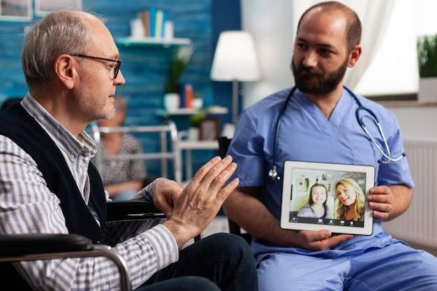Specialist asisstant man holding tablet computer in hands while pensioner male patient greeting friends